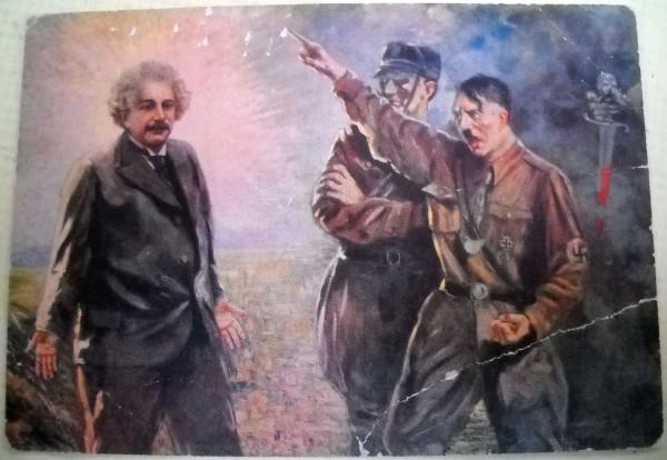 """Um incomum e raro cartão postal com propaganda anti-Nazi a partir de 1934, mostrando Hitler expulsando Einstein da Alemanha, intitulado """"a ignomínia do século 20."""" É uma das representações visuais mais flagrantes de Einstein como um """"santo científico""""."""